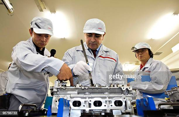 Carlos Ghosn president and chief executive officer of Nissan Motor Co center is given a tour of the automaker's engine assembly plant in Yokohama...