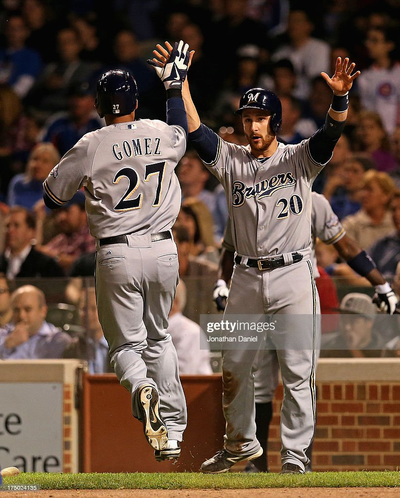 Carlos Gomez #27 and <a gi-track='captionPersonalityLinkClicked' href=/galleries/search?phrase=Jonathan+Lucroy&family=editorial&specificpeople=5732413 ng-click='$event.stopPropagation()'>Jonathan Lucroy</a> #20 of the Milwaukee Brewers celebrate after scoring runs in the 9th inning against the Chicago Cubs at Wrigley Field on July 29, 2013 in Chicago, Illinois.