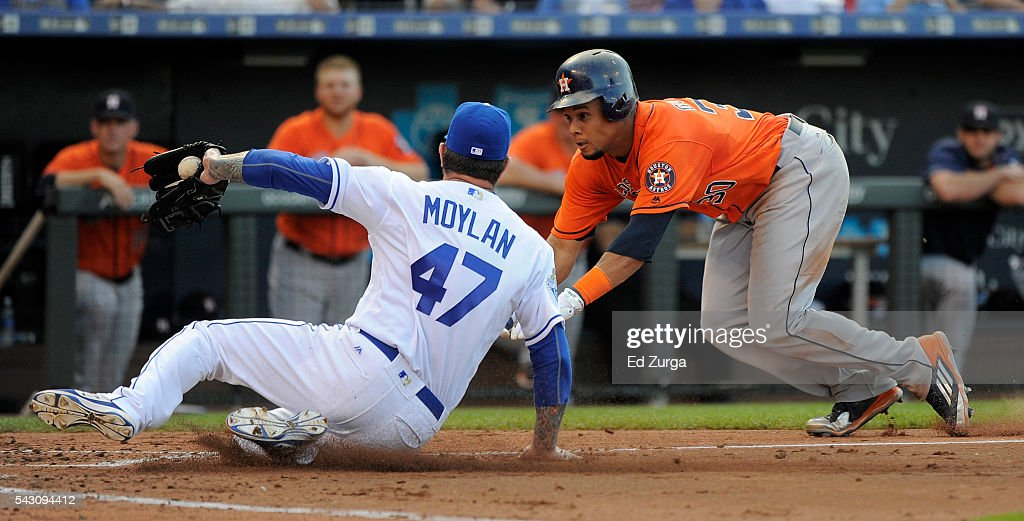 Carlos Gomez of the Houston Astros dives as he tries to score against Peter Moylan of the Kansas City Royals on a wild pitch in the third inning at...