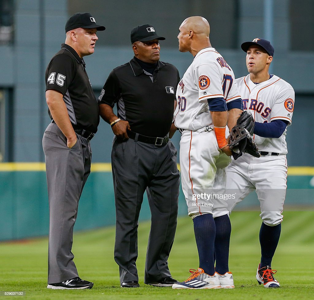 Carlos Gomez of the Houston Astros is held back by George Springer as he argues with umpires Jeff Nelson and Lasz Diaz as he took the field in the...