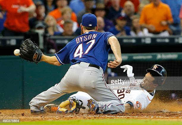Carlos Gomez of the Houston Astros slides into home under the tag of Sam Dyson of the Texas Rangers during the eighth inning at Minute Maid Park on...