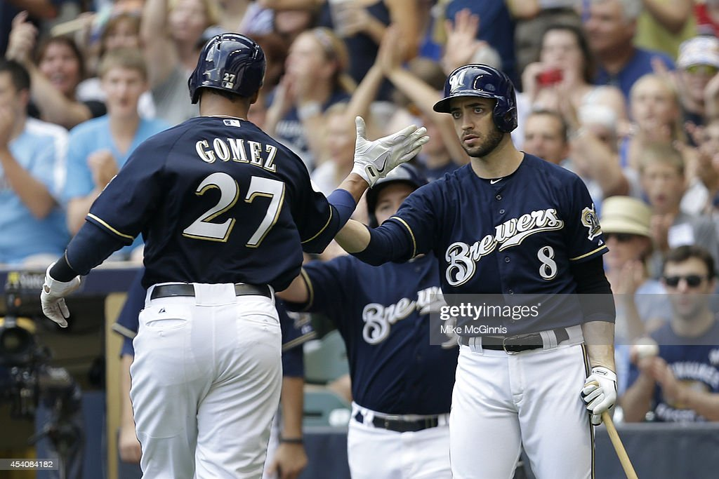 Carlos Gomez #27 of the Milwaukee Brewers celebrates after reaching home plate on a single hit by Jonathan Lucroy in the bottom of the second inning against the Pittsburgh Pirates at Miller Park on August 24, 2014 in Milwaukee, Wisconsin.