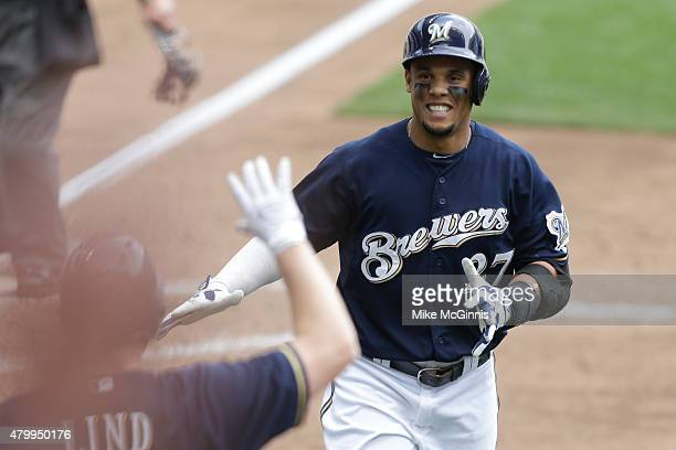 Carlos Gomez of the Milwaukee Brewers celebrates with Adam Lind after hitting a solo home run in the sixth inning against the Atlanta Braves at...