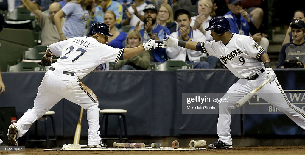 Carlos Gomez #27 of the Milwaukee Brewers celebrates with <a gi-track='captionPersonalityLinkClicked' href=/galleries/search?phrase=Jean+Segura&family=editorial&specificpeople=7521808 ng-click='$event.stopPropagation()'>Jean Segura</a> #9 after crossing home plate in the bottom of the second inning against the San Diego Padres at Miller Park on October 3, 2012 in Milwaukee, Wisconsin.
