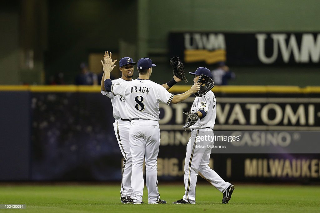 Carlos Gomez #27 of the Milwaukee Brewers celebrates with Norichika Aoki #7 and Ryan Braun #8 after the win over the San Diego Padres at Miller Park on October 2, 2012 in Milwaukee, Wisconsin.