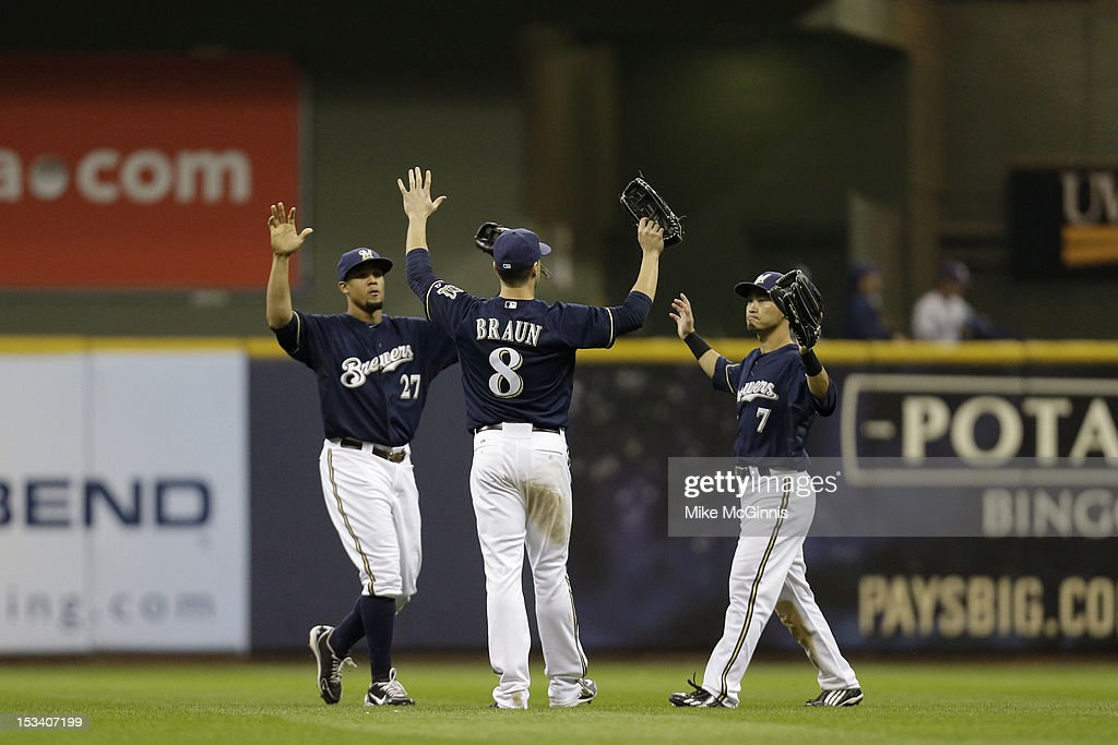 Carlos Gomez #27 of the Milwaukee Brewers celebrates with Ryan Braun #8 and Norichika Aoki #7 after a 5-3 win over the San Diego Padres at Miller Park on October 1, 2012 in Milwaukee, Wisconsin.