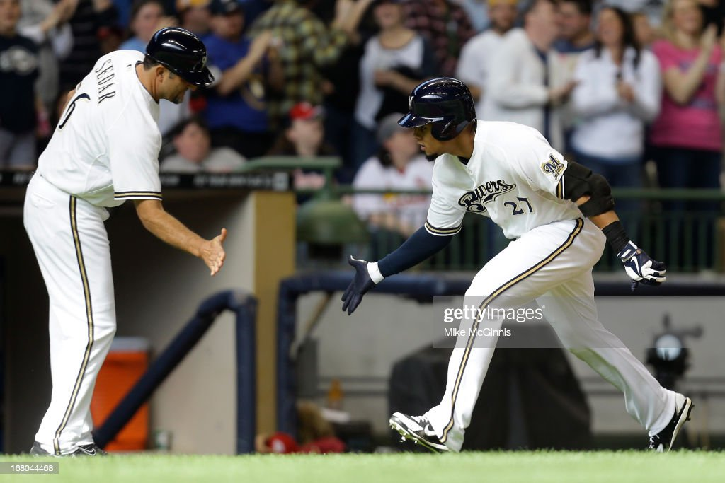 Carlos Gomez #27 of the Milwaukee Brewers celebrates with Third Base Coach Ed Sedar as he runs the bases after hitting a solo home run in the bottom of the sixth inning against the St. Louis Cardinals at Miller Park on May 04, 2013 in Milwaukee, Wisconsin.