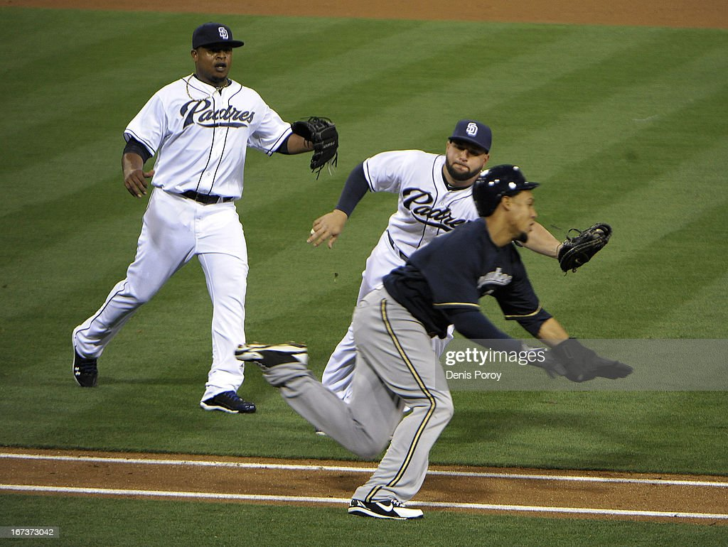 Carlos Gomez #27 of the Milwaukee Brewers dives past the tag of Yonder Alonso #23 of the San Diego Padres as Edinson Volquez #37 looks on during the second inning of a baseball game at Petco Park on April 24, 2013 in San Diego, California. Gomez was safe at first on the bunt.