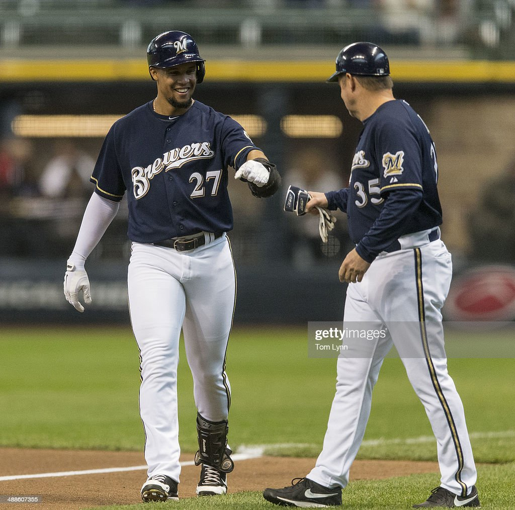 Carlos Gomez #27 of the Milwaukee Brewers gets a fist bump from first base coach Garth Iorg #35 after beating out a bunt off of <a gi-track='captionPersonalityLinkClicked' href=/galleries/search?phrase=Bronson+Arroyo&family=editorial&specificpeople=204136 ng-click='$event.stopPropagation()'>Bronson Arroyo</a> #61 of the Arizona Diamondbacks at Miller Park on May 7, 2014 in Milwaukee, Wisconsin.
