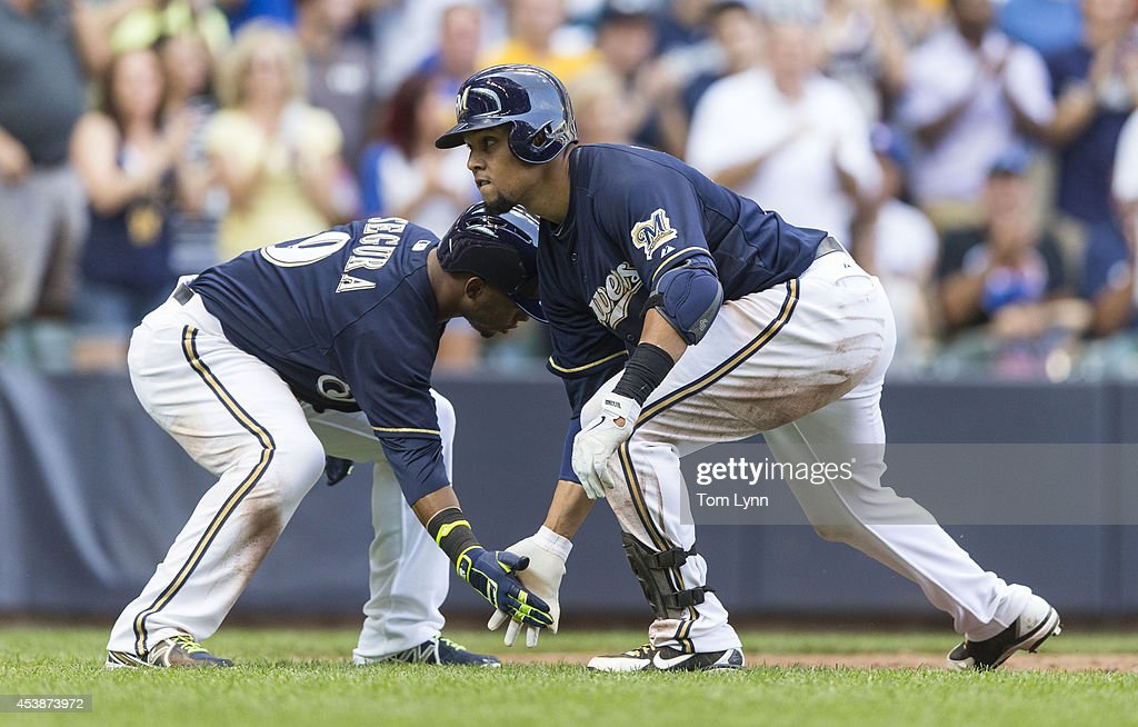 Carlos Gomez #27 of the Milwaukee Brewers gets a low five from teammate Jean Segura #9 after hitting a two run home run against the Toronto Blue Jays at Miller Park on August 20, 2014 in Milwaukee, Wisconsin.