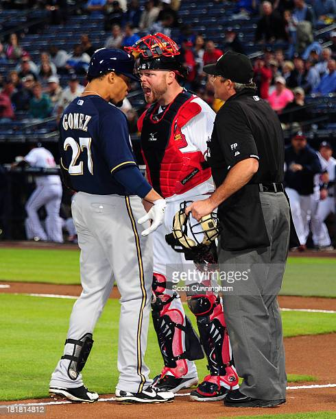 Carlos Gomez of the Milwaukee Brewers is confranted at home plate by Brian McCann of the Atlanta Braves after hitting a first inning home run at...