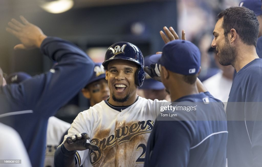 Carlos Gomez #27 of the Milwaukee Brewers is greeted by teammates after scoring against the San Francisco Giants during the second inning at Miller Park on April 18, 2013 in Milwaukee, Wisconsin.