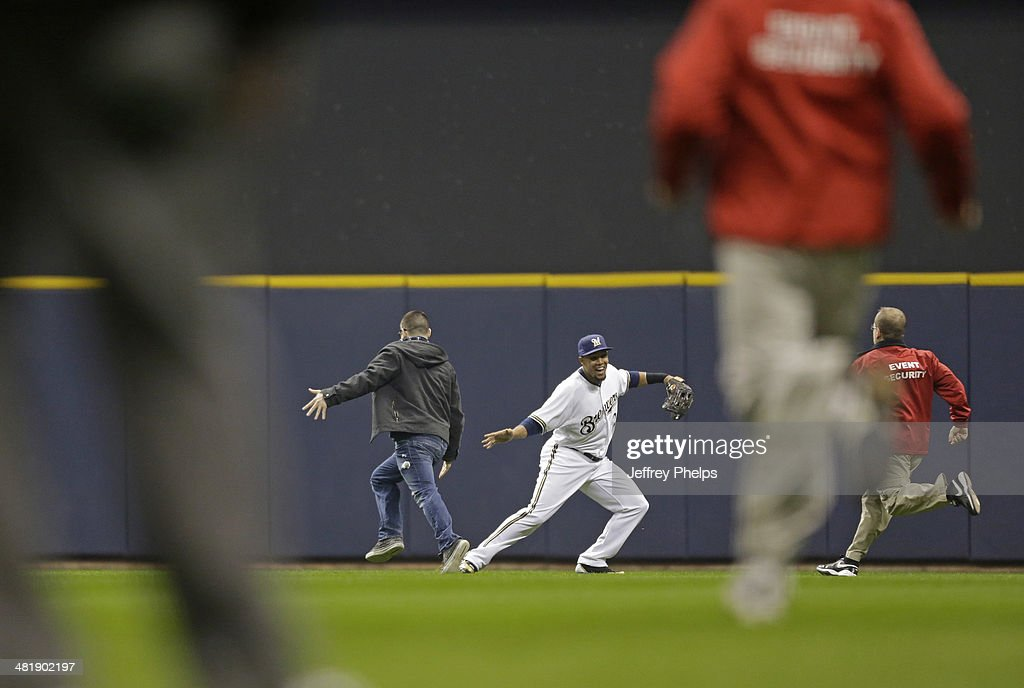 Carlos Gomez #27 of the Milwaukee Brewers low-fives a fan who ran onto the playing field in the third inning of a game against the Atlanta Braves at Miller Park on April 1, 2014 in Milwaukee, Wisconsin.
