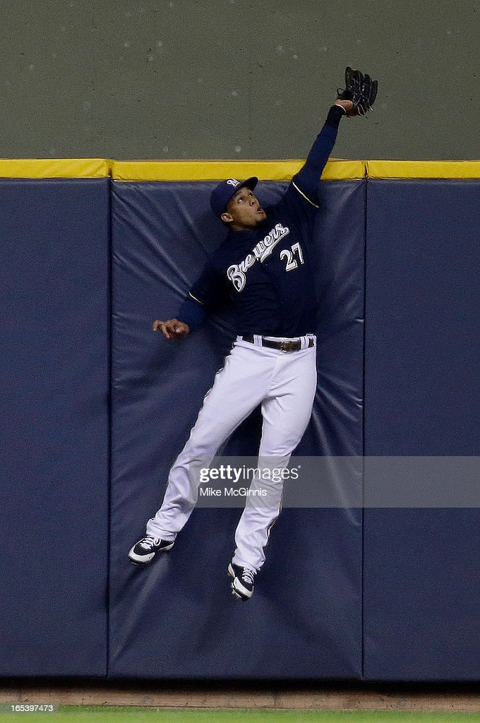 Carlos Gomez #27 of the Milwaukee Brewers robs Carlos Gonzalez of the Colorado Rockies (not pictured) of a home run in the top of the sixth inning at Miller Park on April 3, 2013 in Milwaukee, Wisconsin.