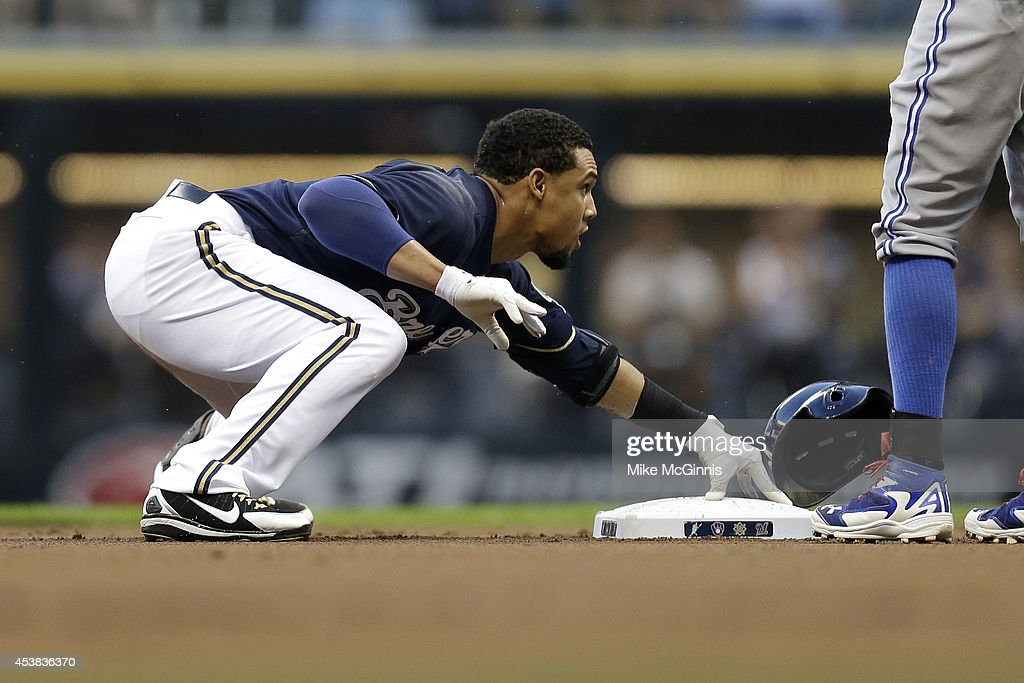 Carlos Gomez #27 of the Milwaukee Brewers slides into second base with a double in the top of the first inning against the Toronto Blue Jays during the Interleague game at Miller Park on August 19, 2014 in Milwaukee, Wisconsin.