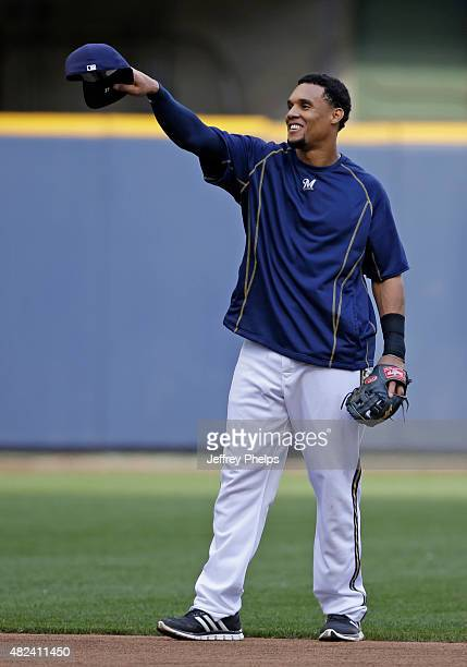 Carlos Gomez of the Milwaukee Brewers tips his hat with teammates before their game against the Chicago Cubs at Miller Park on July 30 2015 in...