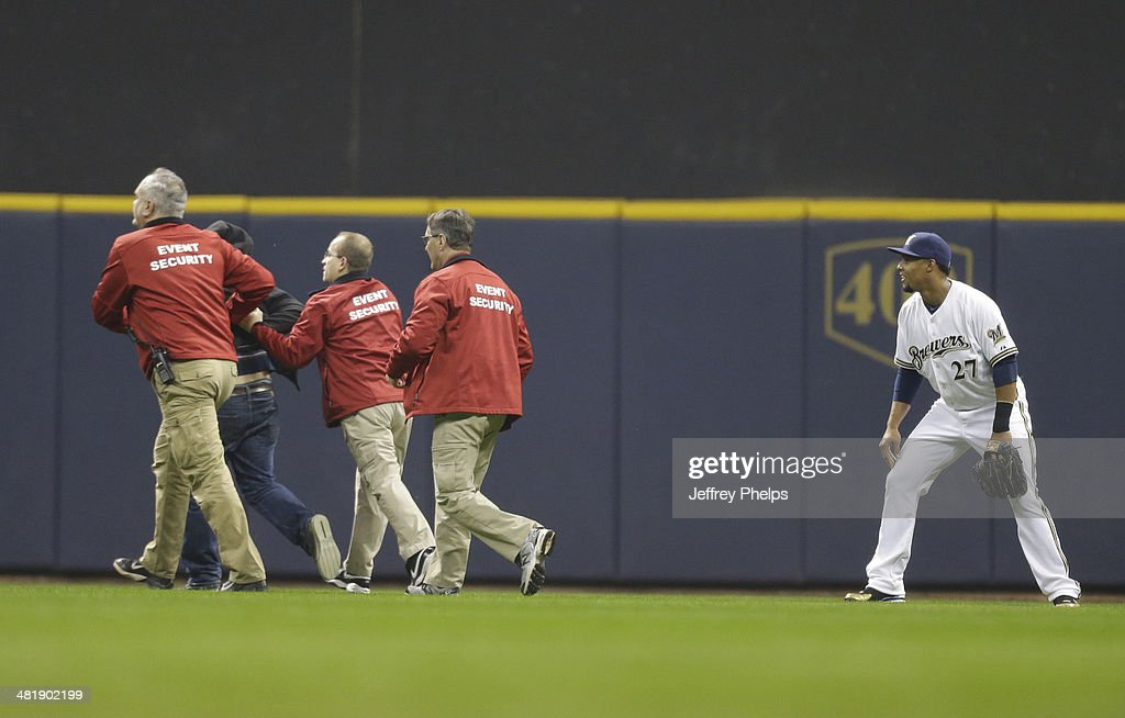 Carlos Gomez #27 of the Milwaukee Brewers watches as security grabs a fan who ran onto the playing field in the third inning of a game against the Atlanta Braves at Miller Park on April 1, 2014 in Milwaukee, Wisconsin.