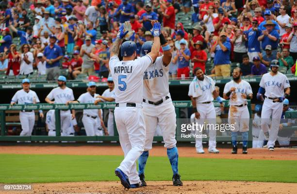 Carlos Gomez of the Texas Rangers after scoring congratulates Mike Napoli for hitting a two run home run against the Seattle Mariners at Globe Life...