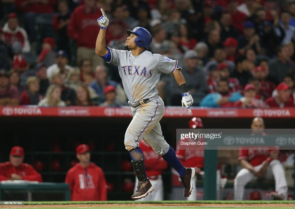 Carlos Gomez #14 of the Texas Rangers celebrates as he runs home after hitting a solo home run in the seventh inning against the Los Angeles Angels of Anaheim at Angel Stadium of Anaheim on April 12, 2017 in Anaheim, California.