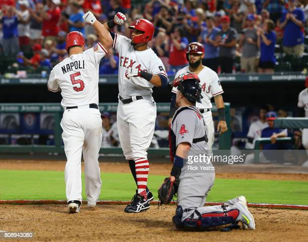 Carlos Gomez of the Texas Rangers congratulates Mike Napoli on Napoli's threerun home run in the eighth inning as Christian Vazquez of the Boston Red...