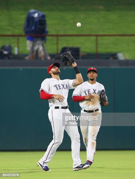 Carlos Gomez of the Texas Rangers looks on as Joey Gallo fields a fly ball in the seventh inning against the Seattle Mariners at Globe Life Park in...