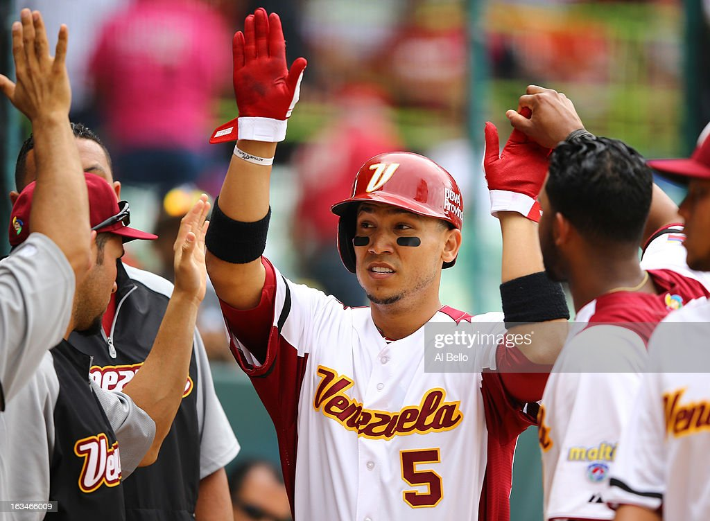 Carlos Gomez #5 of Venezuela celebrates scoring a run against Spain during the first round of the World Baseball Classic at Hiram Bithorn Stadium on March 10, 2013 in San Juan, Puerto Rico.