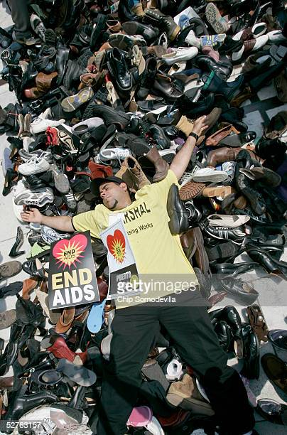 Carlos Gonzales of Philadelphia lays down on top of thousands of pairs of shoes while joining thousands of people who live with HIV/AIDS and their...