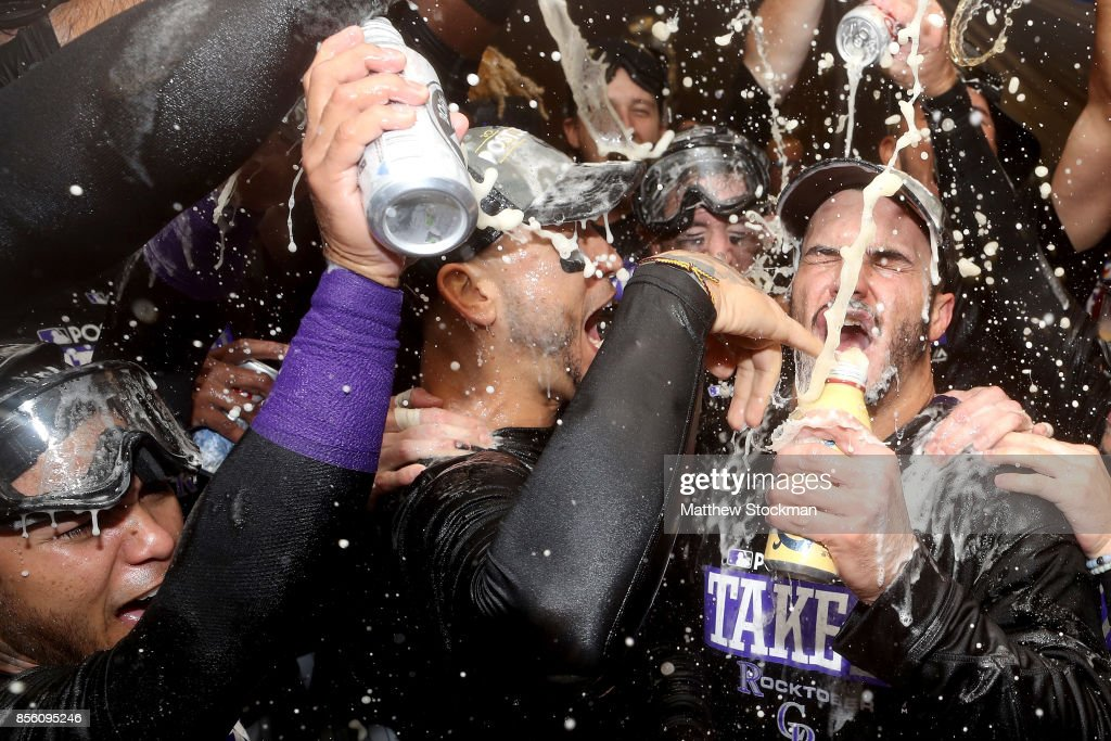 Carlos Gonzalez #5 and Nolan Arenado #28 of the Colorado Rockies are doused by their teammates in the lockerroom at Coors Field on September 30, 2017 in Denver, Colorado. Although losing 5-3 to the Los Angeles Dodgers, the Rockies celebrated clinching a wild card spot in the post season.