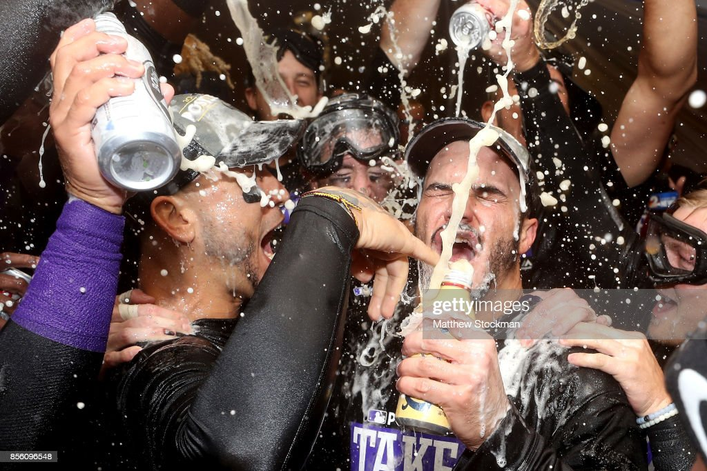 Carlos Gonzalez #5 and Nolan Arenado #28 of the Colorado Rockies are doused by his teammates in the lockerroom at Coors Field on September 30, 2017 in Denver, Colorado. Although losing 5-3 to the Los Angeles Dodgers, the Rockies celebrated clinching a wild card spot in the post season.