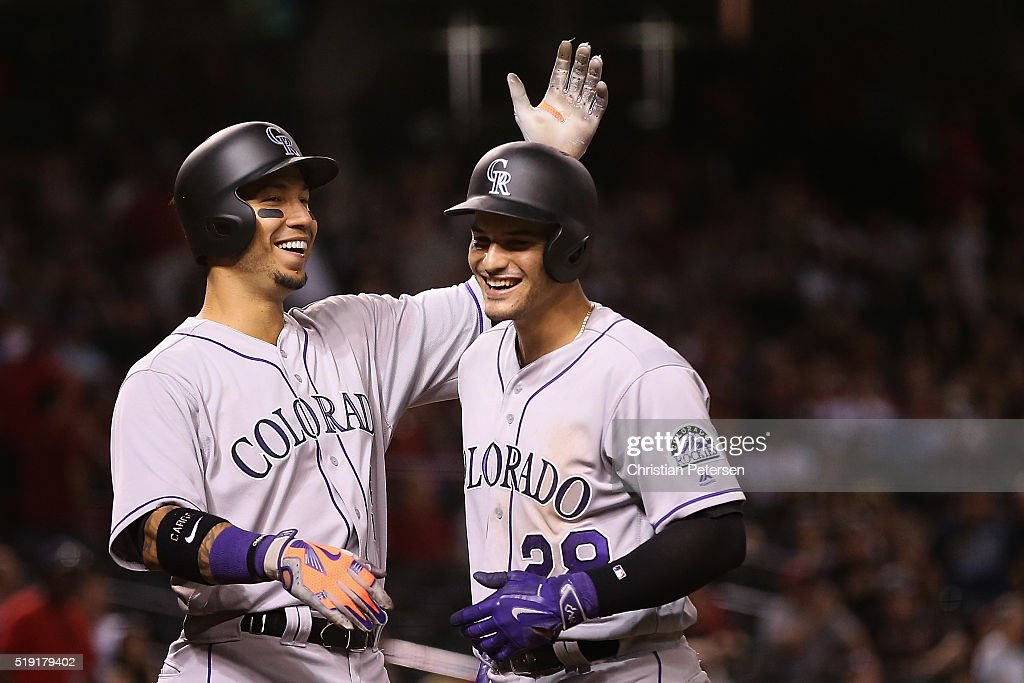 Carlos Gonzalez #5 and Nolan Arenado #28 of the Colorado Rockies celebrate after Arenado hit a three-run home run against the Arizona Diamondbacks during the eighth inning of the MLB opening day game at Chase Field on April 4, 2016 in Phoenix, Arizona.