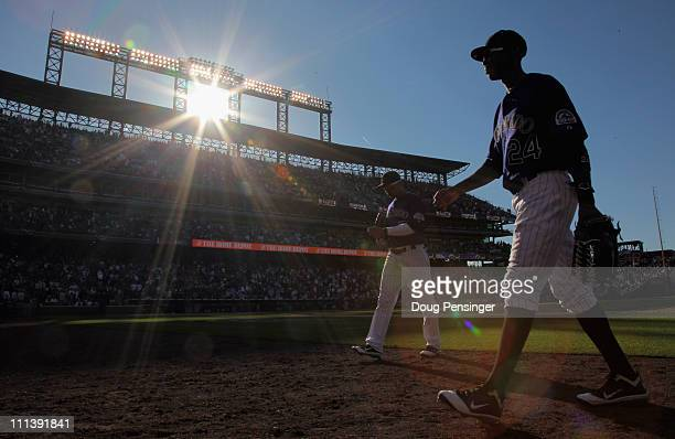 Carlos Gonzalez of the Colorado Rockies and Dexter Fowler of the Colorado Rockies head to the dugout against the Arizona Diamondbacks during Opening...