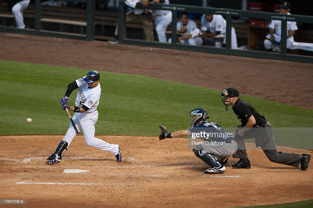 Carlos Gonzalez of the Colorado Rockies bats as Nick Hundley of the San Diego Padres catches and umpire Jeff Nelson calls balls and strikes during a...