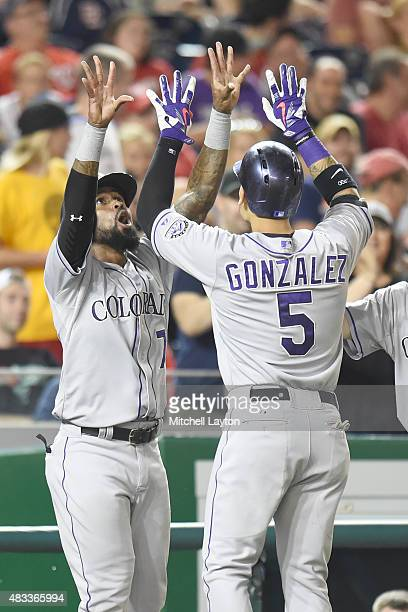 Carlos Gonzalez of the Colorado Rockies celebrates a grand slam home run with Jose Reyes in the eight inning during a baseball game against the...