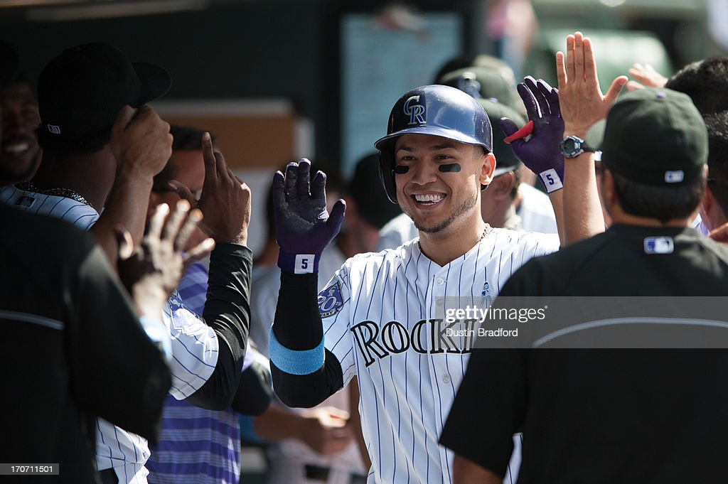 Carlos Gonzalez #5 of the Colorado Rockies celebrates a two-run home run with teammates in the dugout during a game against the Philadelphia Phillies at Coors Field on June 16, 2013 in Denver, Colorado. The Rockies beat the Phillies 5-2.