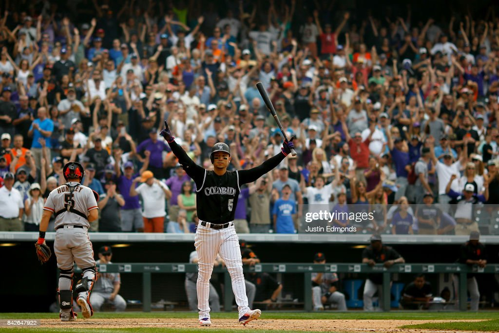 Carlos Gonzalez #5 of the Colorado Rockies celebrates after walking in the ninth inning with the bases loaded that gave the Rockies the 4-3 victory as Nick Hundley #5 of the San Francisco Giants walks off the field and fans cheer at Coors Field on September 4, 2017 in Denver, Colorado.