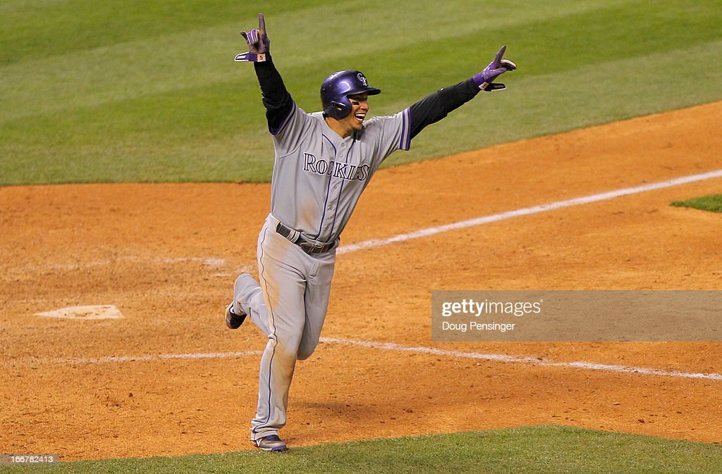 Carlos Gonzalez #5 of the Colorado Rockies celebrates as he scores the game winning run on an RBI single by Jordan Pacheco #15 of the Colorado Rockies to defeat the New York Mets 9-8 in 10 innings at Coors Field on April 16, 2013 in Denver, Colorado.