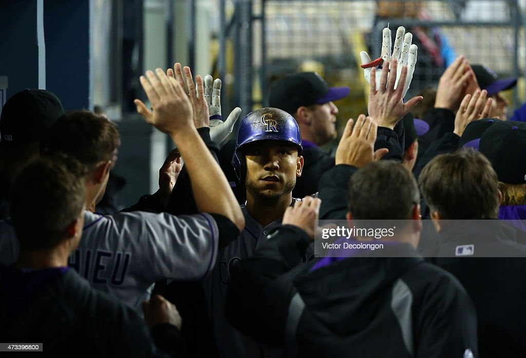 Carlos Gonzalez #5 of the Colorado Rockies celebrates with high-fives in the dugout with his teammates after hitting a three-run home run take a 5-4 lead in the ninth inning against the Los Angeles Dodgers during the MLB game at Dodger Stadium on May 14, 2015 in Los Angeles, California. The Rockies defeated the Dodgers 5-4.