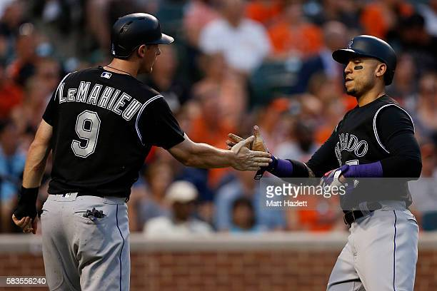 Carlos Gonzalez of the Colorado Rockies celebrates with teammate DJ LeMahieu after scoring in the third inning against the Baltimore Orioles at...