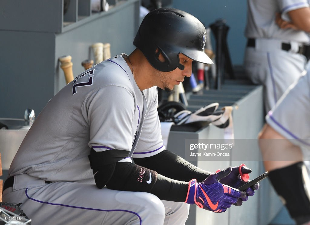 Carlos Gonzalez #5 of the Colorado Rockies checks an iPad before going up to bat in the ninth inning of the game against the Los Angeles Dodgers at Dodger Stadium on September 10, 2017 in Los Angeles, California.