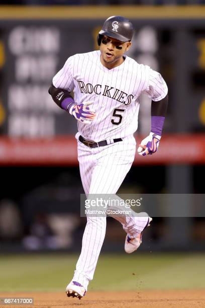 Carlos Gonzalez of the Colorado Rockies circles the bases after hitting a home run in the fourth inning against the San Diego Padres at Coors Field...