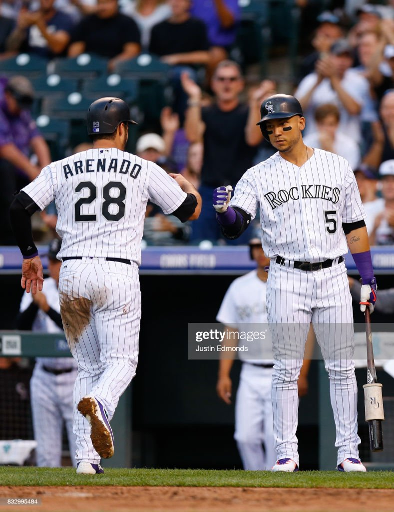 Carlos Gonzalez #5 of the Colorado Rockies congratulates Nolan Arenado #28 on scoring during the first inning against the Atlanta Braves at Coors Field on August 16, 2017 in Denver, Colorado.