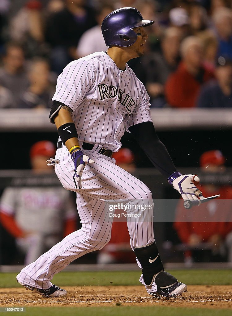 Carlos Gonzalez #5 of the Colorado Rockies drops the handle of his bat as he hits a broken bat single off of Mario Hollands #43 of the Philadelphia Phillies in the sixth inning at Coors Field on April 18, 2014 in Denver, Colorado.