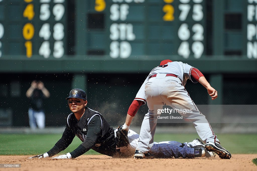 Carlos Gonzalez #5 of the Colorado Rockies escapes the tag of Stephen Drew #6 of the Arizona Diamondbacks during the game at Coors Field on May 27, 2010 in Denver, Colorado.