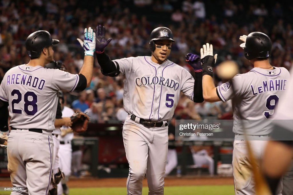 Carlos Gonzalez #5 of the Colorado Rockies high fives Nolan Arenado #28 and DJ LeMahieu #9 after hitting a two run home run against the Arizona Diamondbacks during the seventh inning of the MLB game at Chase Field on September 12, 2017 in Phoenix, Arizona.