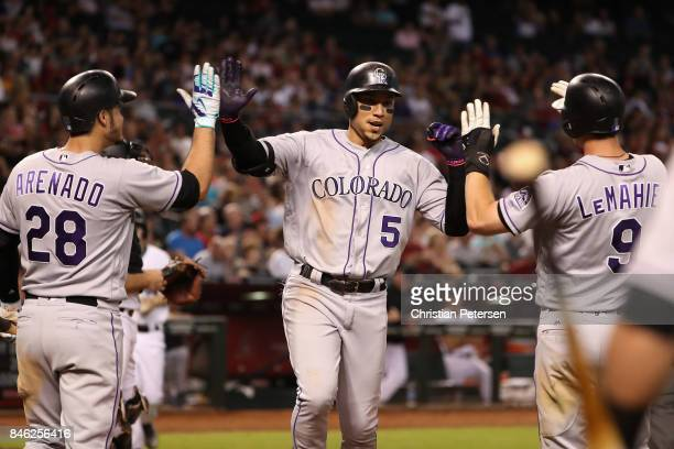 Carlos Gonzalez of the Colorado Rockies high fives Nolan Arenado and DJ LeMahieu after hitting a two run home run against the Arizona Diamondbacks...