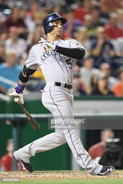 Carlos Gonzalez of the Colorado Rockies hits a grand slam home run in the eight inning during a baseball game against the Washington Nationals at...