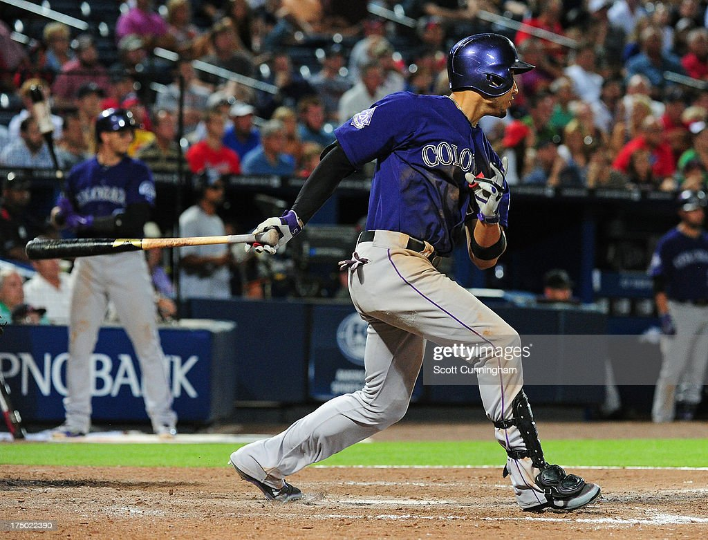 Carlos Gonzalez #5 of the Colorado Rockies hits a run scoring single in the ninth inning for his fifth hit of the game against the Atlanta Braves at Turner Field on July 29, 2013 in Atlanta, Georgia.