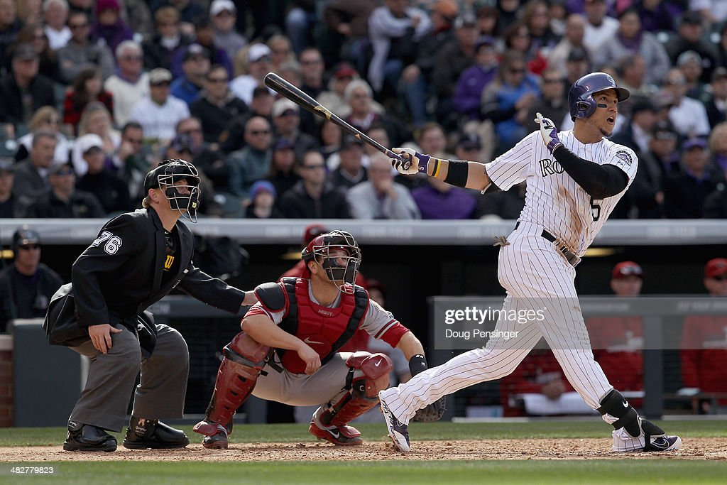 Carlos Gonzalez #5 of the Colorado Rockies hits a two run home run off of Joe Thatcher #54 of the Arizona Diamondbacks as catcher Miguel Montero #26 of the Arizona Diamondbacks and umpire umpire Mike Muchlinski look on as the Rockies took a 8-1 lead in the sixth inning during the home opener at Coors Field on April 4, 2014 in Denver, Colorado.