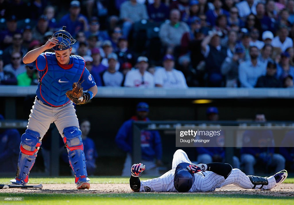 Carlos Gonzalez #5 of the Colorado Rockies hits the deck on an inside pitch as catcher Miguel Montero #47 of the Chicago Cubs retrieves the ball at Coors Field on April 12, 2015 in Denver, Colorado. The Cubs defeated the Rockies 6-5.