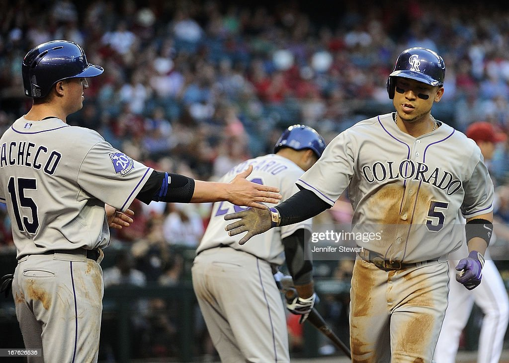 Carlos Gonzalez #5 of the Colorado Rockies is congratulated at home plate by teammate Jordan Pacheco #15 after scoring on an RBI double hit by Michael Cuddyer (not pictured) against the Arizona Diamondbacks in the first inning at Chase Field on April 26, 2013 in Phoenix, Arizona.
